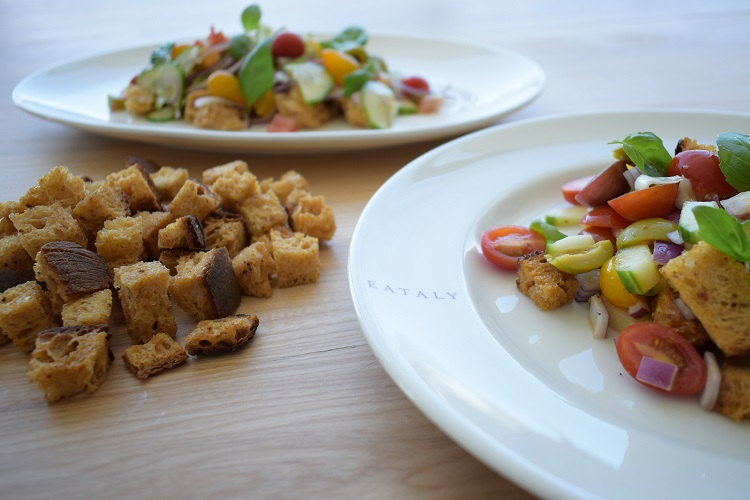 Two plates of panzanella, a Tuscan bread salad with tomatoes, onions, and leftover stale bread