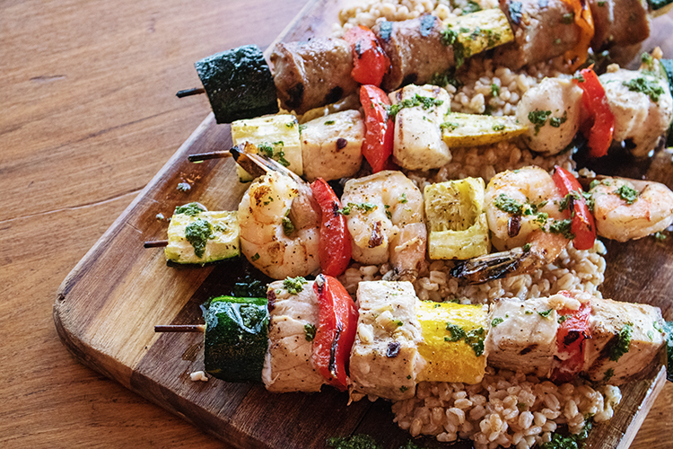 grilled skewers with chicken, shrimp, vegetables and farro