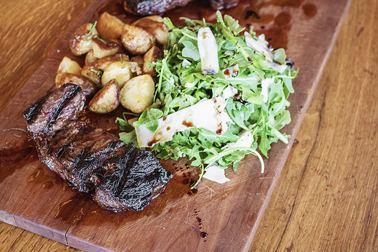 grilled steak with salad and roasted potatoes