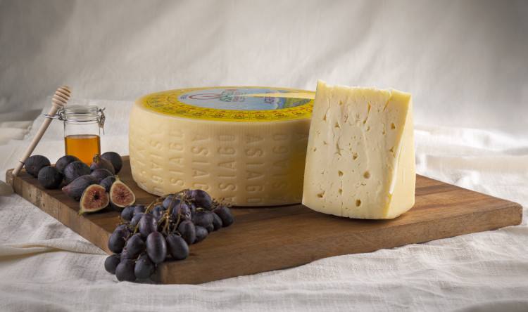 Wheel of Asiago cheese with grapes